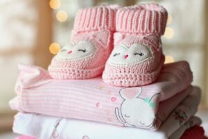packed baby clothes with pink shoes on top